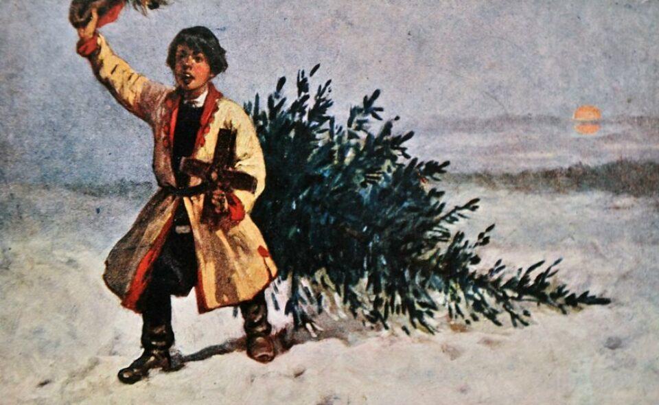 Chłopiec w stroju ludowym ciągnący choinkę.