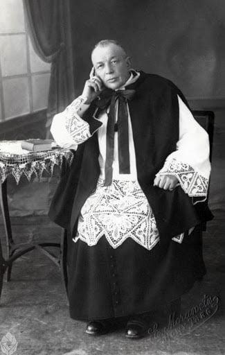 Czarnobiałe zdjęcie siedzącego księdza