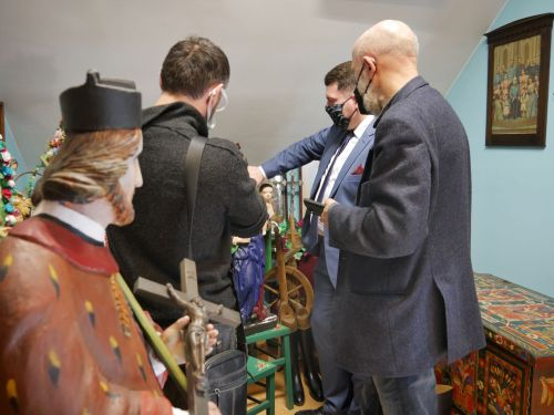 trzech mężczyzn ogląda eksponaty w pomieszczeniu muzealnym