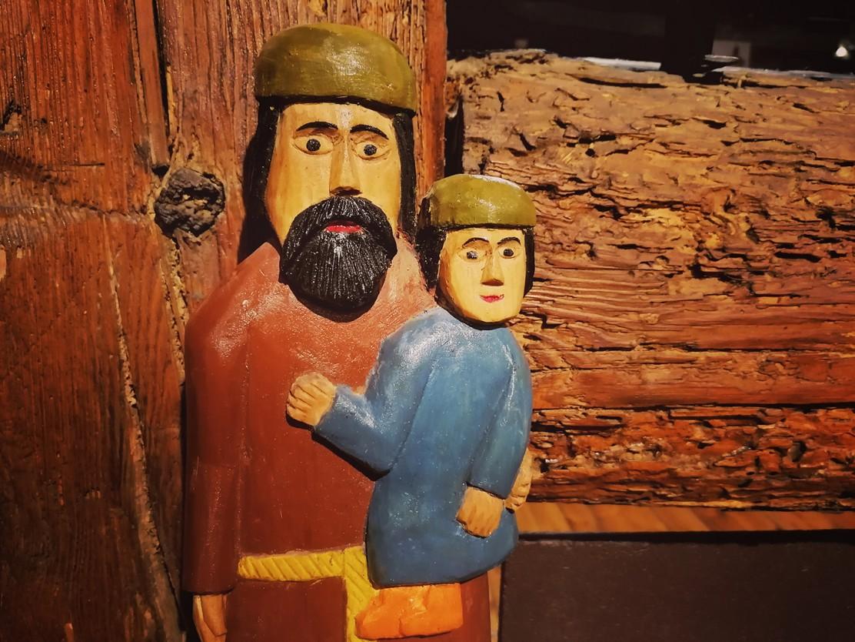 zdjęcie przedstawia rzeźbę ludową - brodaty mężczyzna z dzieckiem na ręku